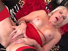 this busty granny in sexy lingerie is masturbating on the bed while on webcam